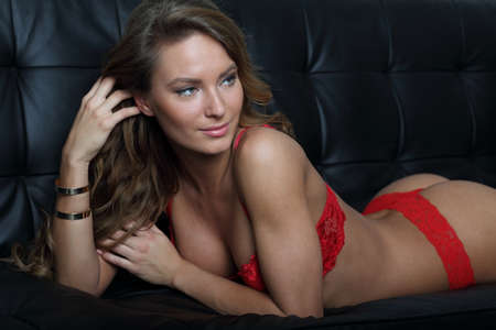big boobs: Modelo de lencería perfecta en rojo en el sofá negro Foto de archivo