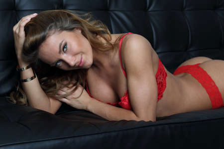 big boobs: Perfect lingerie model in red on black sofa
