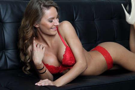 big boobs: Modelo de lencer�a perfecta en rojo en el sof� negro Foto de archivo