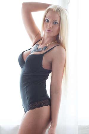 nude blonde woman: Blonde posing in black body in front of a window
