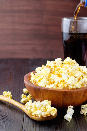 Popcorn in a bowl on wooden background.
