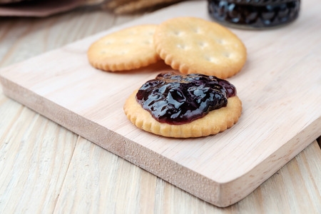 Cracker with jam on woodden background Stock Photo