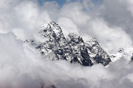 Rocky summit sticking out of clouds, Himalaya Stock Photo - 5388270