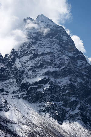 Clouds over rocky unclimbed Peak 5939, Himalaya