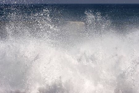roaring sea: Spray and foam from wave hitting the shore