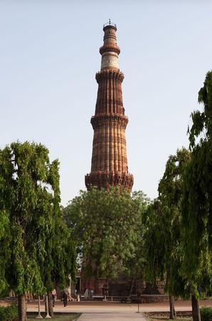 minar: Qutb Minar tower among trees, Delhi, India Stock Photo