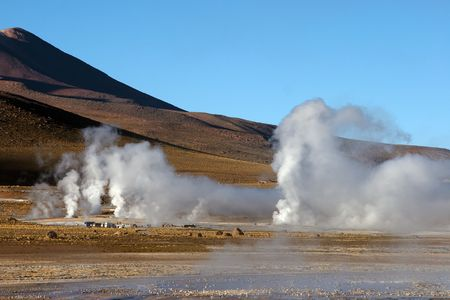 Geyser field with volcano in background, Chile Stock Photo