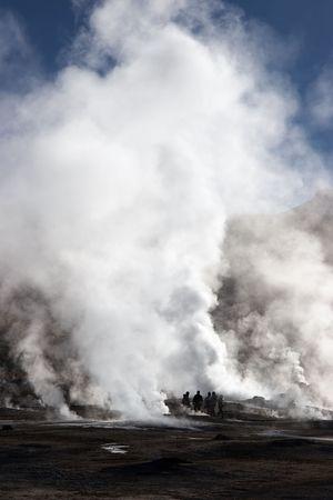 Tourists near erupting geyser, Chile Stock Photo