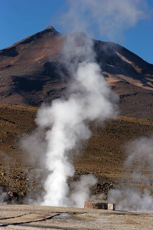 Erupting geyser with volcano in background, Chile Stock Photo