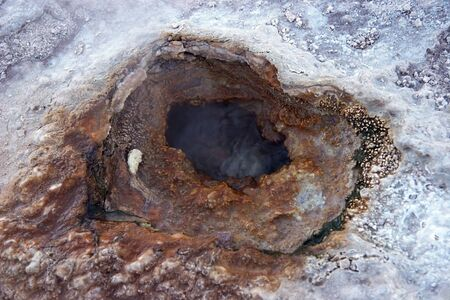 Geyser hole with colored sediments Stock Photo