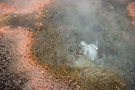 Closeup of a geyser with orange sediment