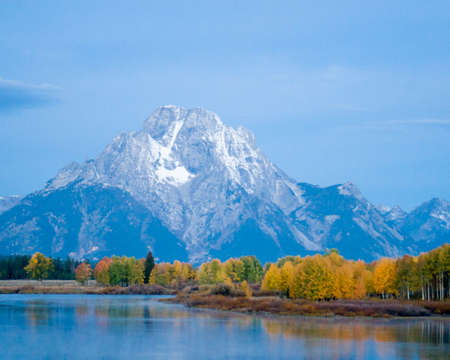 Snow-capped Grand Tetons provide a backdrop for a lazy river refelcting autumn color