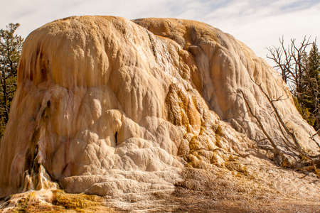 This geological feature at Yellowstone National Park shows evidence of mineral deposits as the mineral-rich water flows down the side.