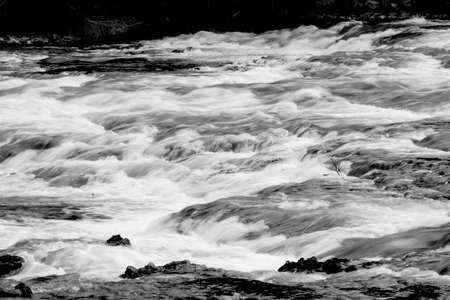 Captured river at 110th of a second to provide a softness that belies the rushing water in Yellowstone National Park. Rendered in black & white to add to the effect. Imagens
