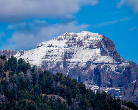A rugged mountain in the Grand Tetons rises against a mostly blue sky