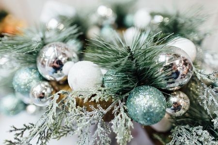 Close-Up of silver baubles hanging from a decorated Christmas tree. Soft selective elective focus