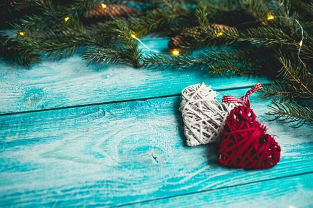 Christmas hearts on a blue wooden table with Christmas tree. Mock up. Stock Photo