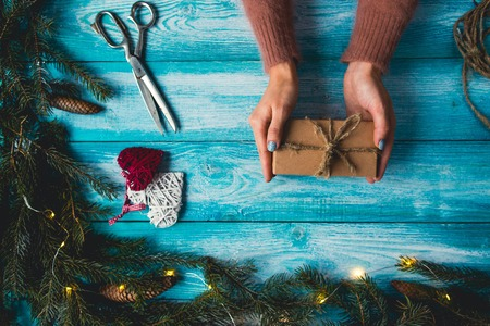 woman's hands: Concept of Christmas items on a blue wodden table. Womans hands wrapping Christmas gift.