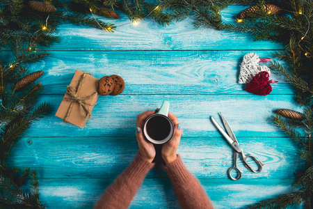 Girl holding a cup of hot cocoa on a wooden blue background. Christmas concept.