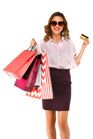 Shopping woman with shopping bags holding credit card, isolated on white background. Online shopping concept