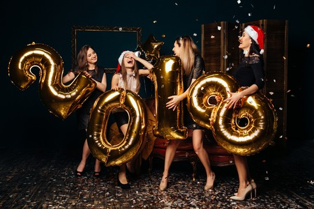 Group of cheerful young women in Christmas hats holding gold colored numbers and throwing confetti at New Year party
