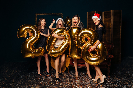 Group of girlfriends in Santa hats have fun on celebrating New year Reklamní fotografie