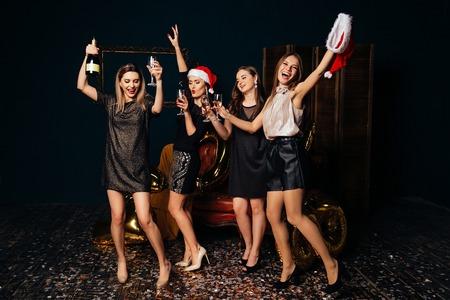 Dancing beautiful women with champagne celebrating Christmas Foto de archivo
