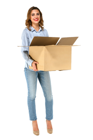 Standing beautiful happy girl holding open box dressed up in blouse, jeans on high-heel shoes, in full size length, on white background.