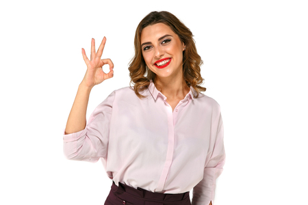 Portrait of happy beautiful business woman showing okay gesture, looking at camera, smiling, with red lipstick . Isolated over white background. Stock Photo