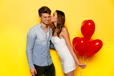 Woman holding red balloons kissing her boyfriend, standing on yellow background. St. Valentines day. Stock Photo