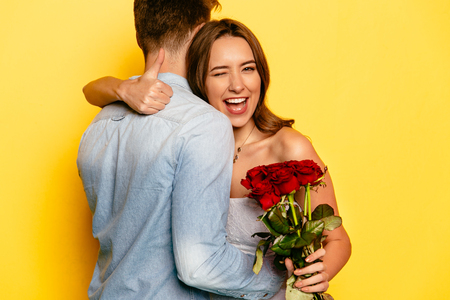 Attractive young woman with red roses winking and showing a thumb while hugging her boyfriend. Celebrating St. Valentine's Day.