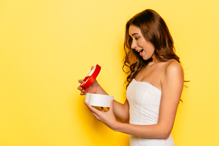 Beautiful girl with wondered face opening gift box, received from her boyfriend on St. Valentines day. Event concept Stock Photo