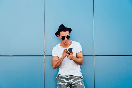 Happy young man in sunglasses and hat typing a message on smartphone, chatting. Outdoors. Stok Fotoğraf