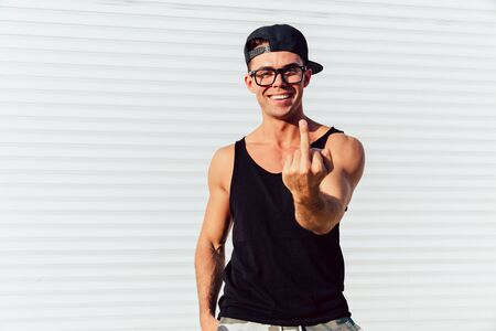 Cheerful stylish man in eyeglasses, showing middle finger, looking at camera, wearing black sleeveless t-shirt and cap. Standing outdoors.