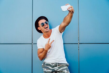 Cheerful stylish man in sunglasses and black hat takes a selfie, showing two fingers, standing against the wall.