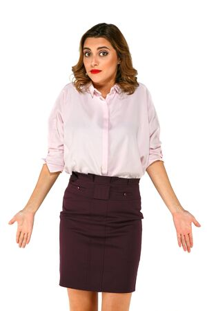 Young pretty woman spreads out her hands with shrugs shoulders because of misunderstanding, dressed up in business clothes on a white background.