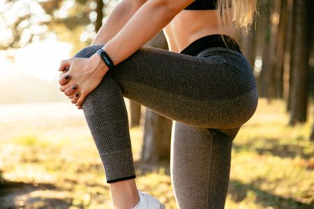 Close-up view of sportive female stretching legs before running, workout outside, in the wood. Dressed in tank top and leggings. Stok Fotoğraf