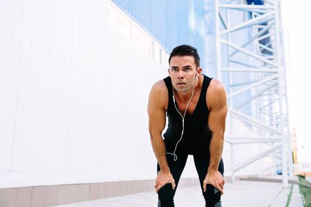Handsome muscular man in headset resting after running, during workout outdoors, wearing black sportswear. Banque d'images