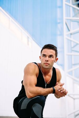 Attractive muscular man in headset, staring into the distance, preparing to workout, outdoors.