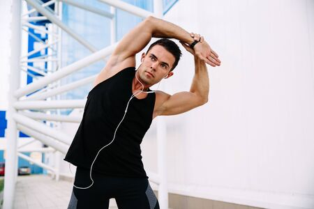 Healthy lifestyle and sport concept. Handsome concentrated man doing stretching exercises for body during training outdoors, listening to music in headphones . Stock Photo