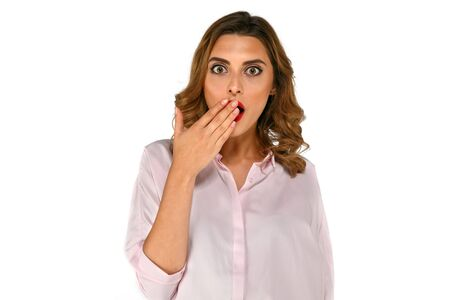 Wondered surprised business woman covering her mouth by the hands with curly hair, dressed up in blouse, on white background