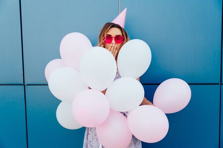 Beautiful young girl looks surprised while standing with air balloons. Wearing pink sunglasses and party hat, outside.