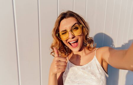 Charming smiling girl in yellow eyeglasses winking and showing a thumb up while taking a selfie. Outdoors 版權商用圖片