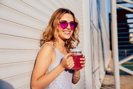 Smiling attractive girl in glamour sunglasses, drinking fresh beverage from big glass, spending time with pleasure outdoors. Dressed in summer dress. Stock Photo