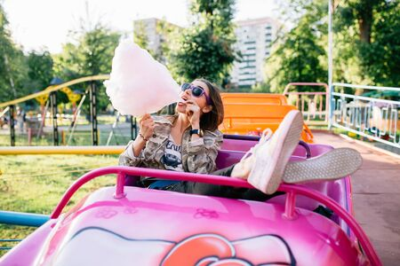Happy charming young woman eating a cotton candy, while spending time at amusement park, enjoying the sunny day. Wearing sunglasses, in fashionable clothes. Leisure concept. 스톡 콘텐츠