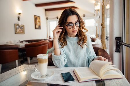 Smart student girl studying in cafe while drinking coffee