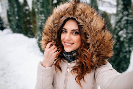 Selfie d'hiver. Belle fille en capuche de fourrure prend selfie en journée d'hiver enneigée Banque d'images
