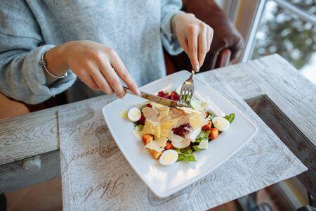 Mujer come una deliciosa ensalada César en un restaurante. De cerca