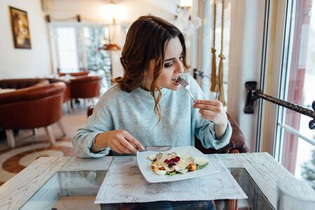 Woman eating tasty vegetable salad in restaurant