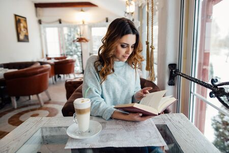 Young woman reading interesting book in cafe while drinking hot coffee